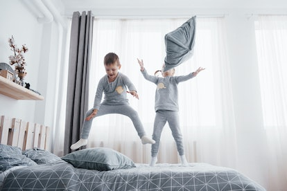 Happy kids playing in white bedroom. Little boy and girl, brother and sister play on the bed wearing pajamas. Family at home