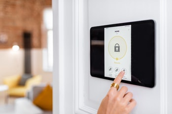 Controlling home alarm system with a digital touch screen panel installed on the wall. Concept of wi...