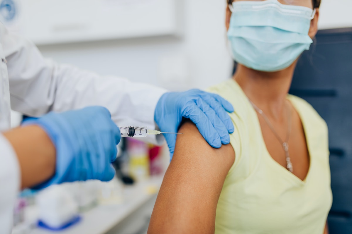 Female doctor or nurse giving shot or vaccine to a patient's shoulder. Vaccination and prevention against flu or virus pandemic.