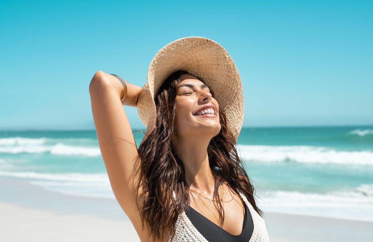 Girl with straw hat enjoying sunbath at beach having the best September 2021, per her zodiac sign.