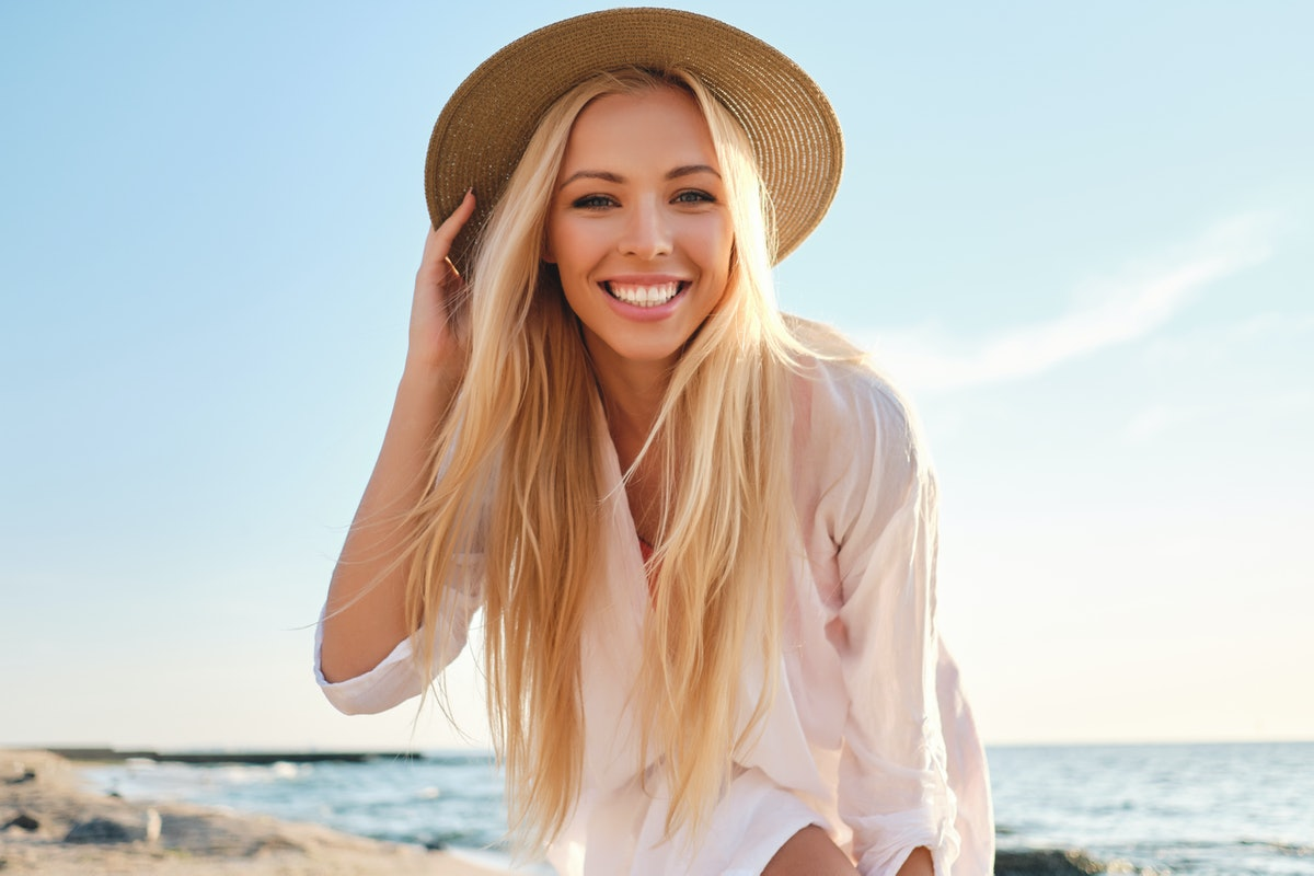 Young attractive smiling blond woman in white shirt and hat joyfully looking in camera with sea on background