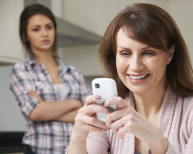 Mother Texts On Mobile Phone As Daughter Watches In Background