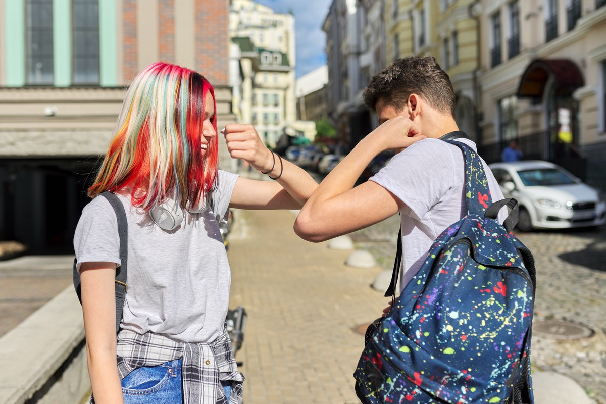 Two teenage friends greet each other by bumping elbows, maintaining distance during pandemic reopening