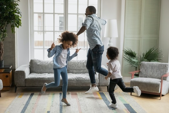 A dad and his two kids having a dance party in the living room