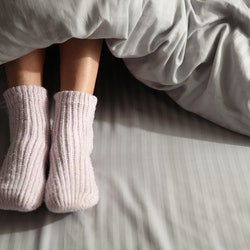 Woman wearing knitted socks under blanket in bed, closeup