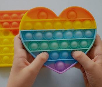 colorful antistress sensory toy fidget push pop it in kid's hands