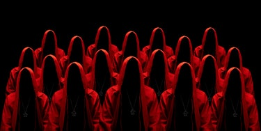People dressed in a red robes looking like a cult members on a dark background. No face. Occult, sec...