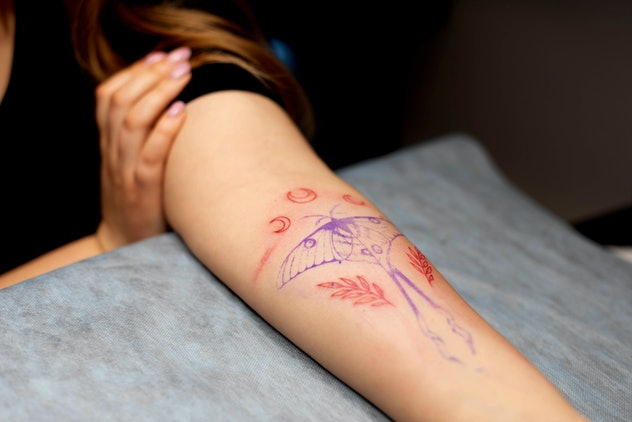 Charming girl with pink hair and tattoos stuffs a tattoo on a woman's hand in a tattoo parlor, creat...