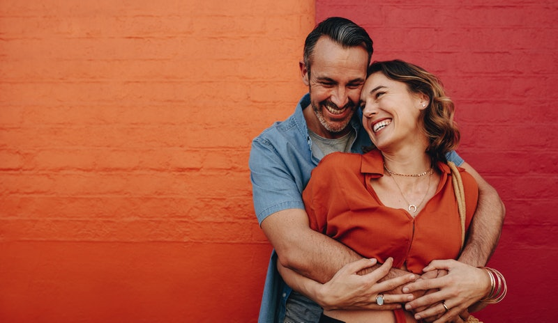 Beautiful couple in love embracing standing against a wall. Romantic couple together on multicolored wall.