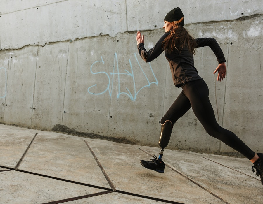 Portrait of disabled athlete woman with prosthetic leg in tracksuit running outdoor along concrete wall