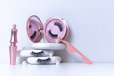 Magnetic fake artificial eyelashes in pink mirror kit, eye liner, tweezers on white background. Home...