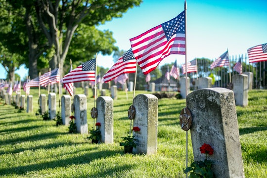 Memorial Day American flags and military grave marker at military cemetery honoring those who sacrificed all in service to their country