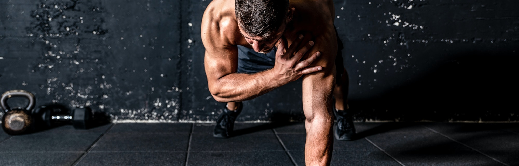 Young sweaty strong and fit muscular man push ups workout with touching his shoulder on one hand in the gym on the floor cross training