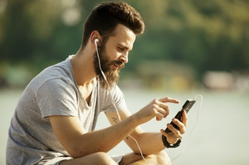 Portrait of a man with beard listening music on mobile phone outdoors