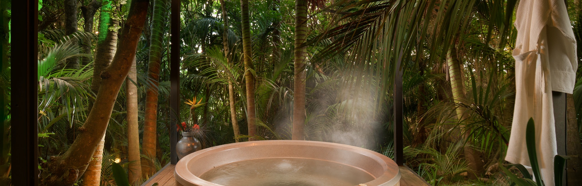 A hot tub under a pagoda sitting in the palm forest