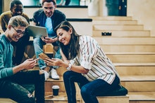 Cheerful millenial woman showing latest feed from social networks to group of multiracial friends, h...