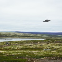 Flying saucer UFO over tundra in the Kola Peninsula in Russia. UFO floating above tundra landscape n...