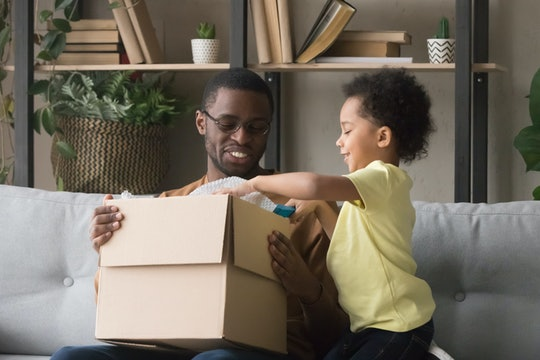 Family african father and little son opens unpack carton box sitting on sofa at home, satisfied clients received parcel. Delivery, shipping shipment, postal service, buying in internet stores concept