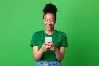 Amazing Application. Portrait of happy black woman using smartphone on green studio wall