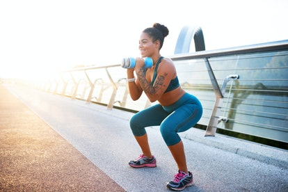 Barbells in arms. Smiling tattooed woman doing sit ups with barbells in arms on nice summer day