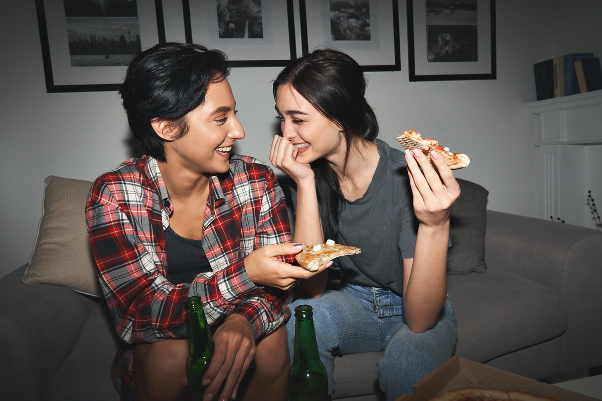Two women celebrating their four-month anniversary with pizza.