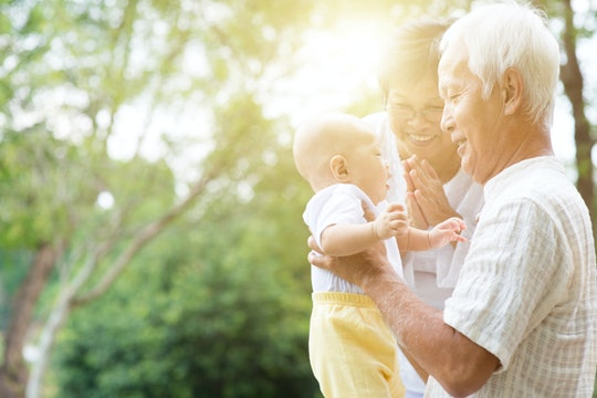 Grandparents holding baby grand baby at outdoor park