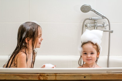 Two little sisters play in a bath with foam.