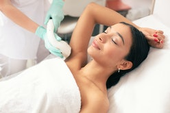 Calm young woman lying with closed eyes and putting on arm up while having laser hair removal proced...