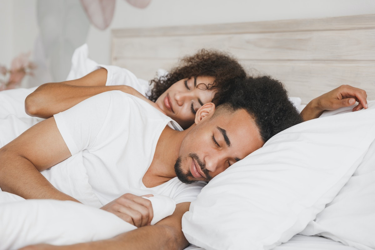 Young calm african loving couple girl guy in t-shirts lying on bed with white sheet pillow blanket indoors in bedroom at home, spending time in room. Rest relax good mood quarantine lifestyle concept