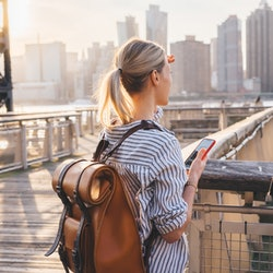 Back view of international tourist with trendy backpack enjoying time for exploring USA megalopolis - New york standing at Brooklyn district and looking around at landscape of big city area