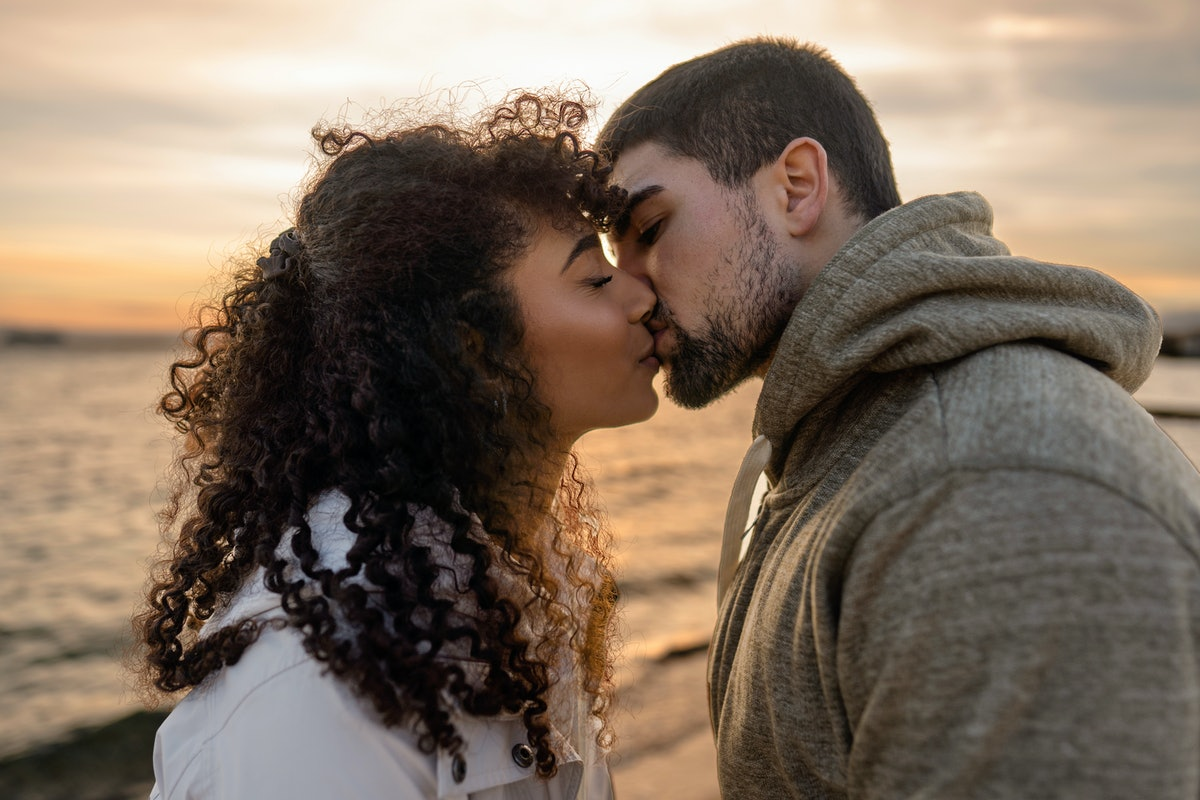 Head and shoulders portrait of young beautiful couple in love kissing at sunset in winter seaside resort with cloudy sky. Two millennials in vacation travel manifesting their heart sentiments outdoor