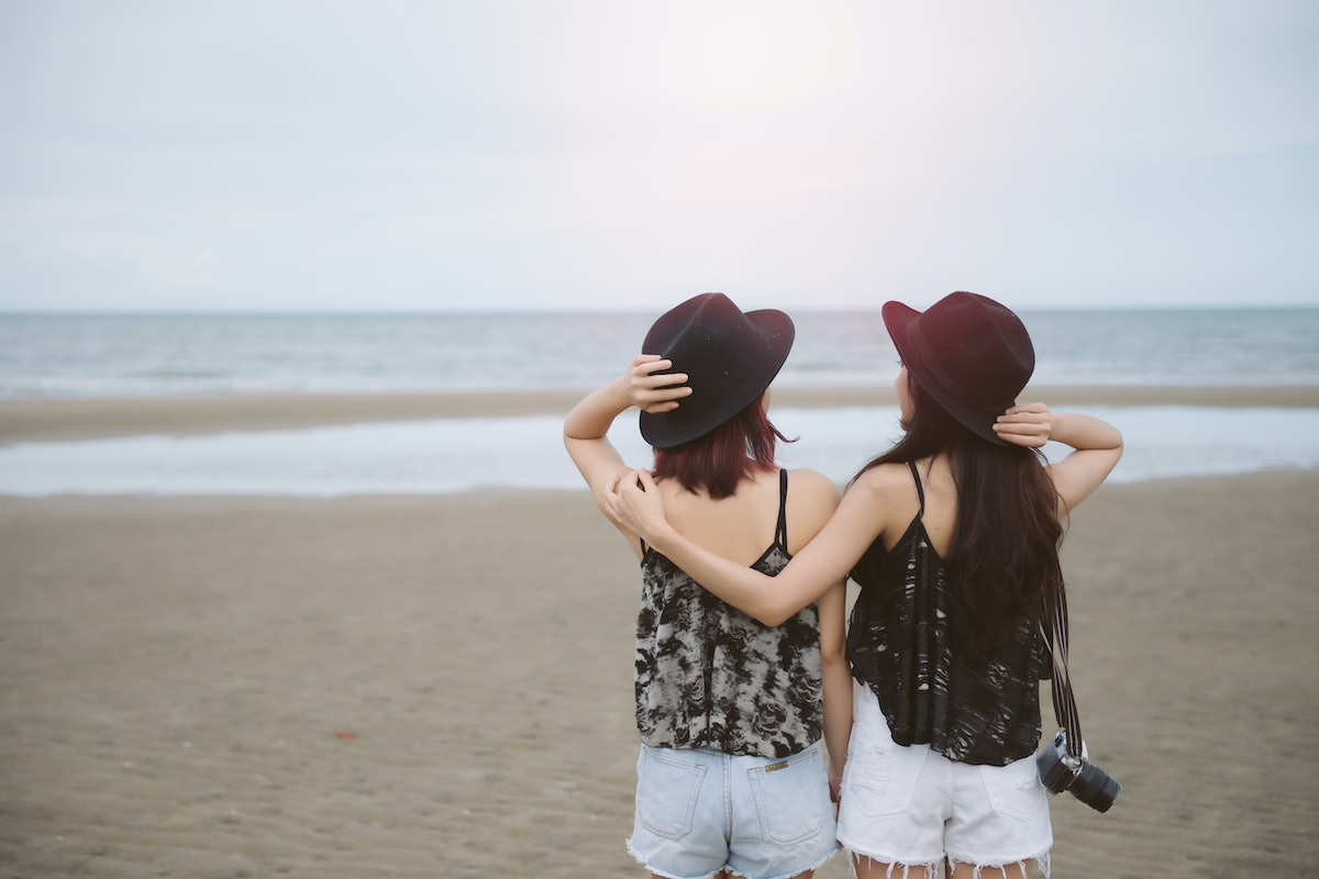 Back view of two woman relax on holiday. Lesbian Couple stand back on beach near sea. Lesbian Couple...