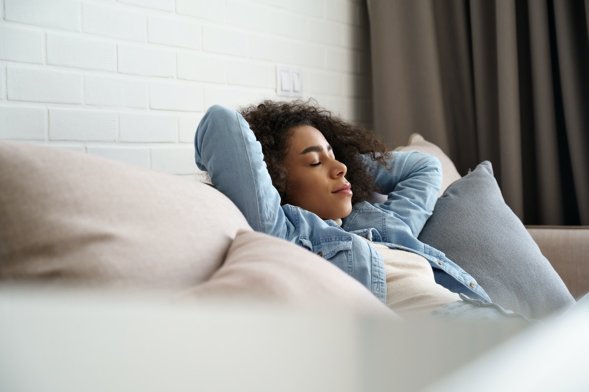Relaxed tired young african american woman napping on comfortable sofa with eyes shut closed. Calm lazy black girl leaning on couch in living room enjoying chill sleeping resting at home concept.