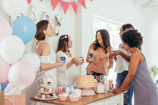 Pregnant woman celebrating baby shower party with female friends at home. Group of multi-ethnic wome...