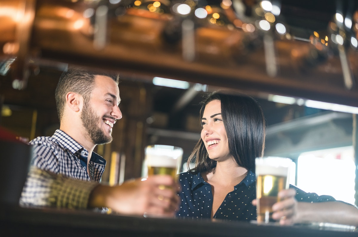 Young couple at beginnings of love story - Pretty woman drinking beer with handsome man at pub - Rel...