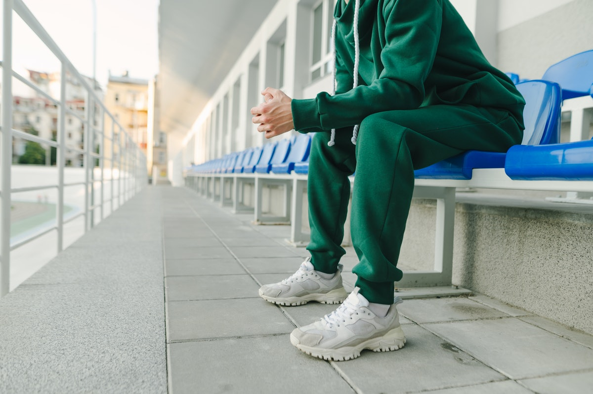 Cropped photo of a young man's legs in a green suit and bloodsuckers, sitting alone in the stands an...