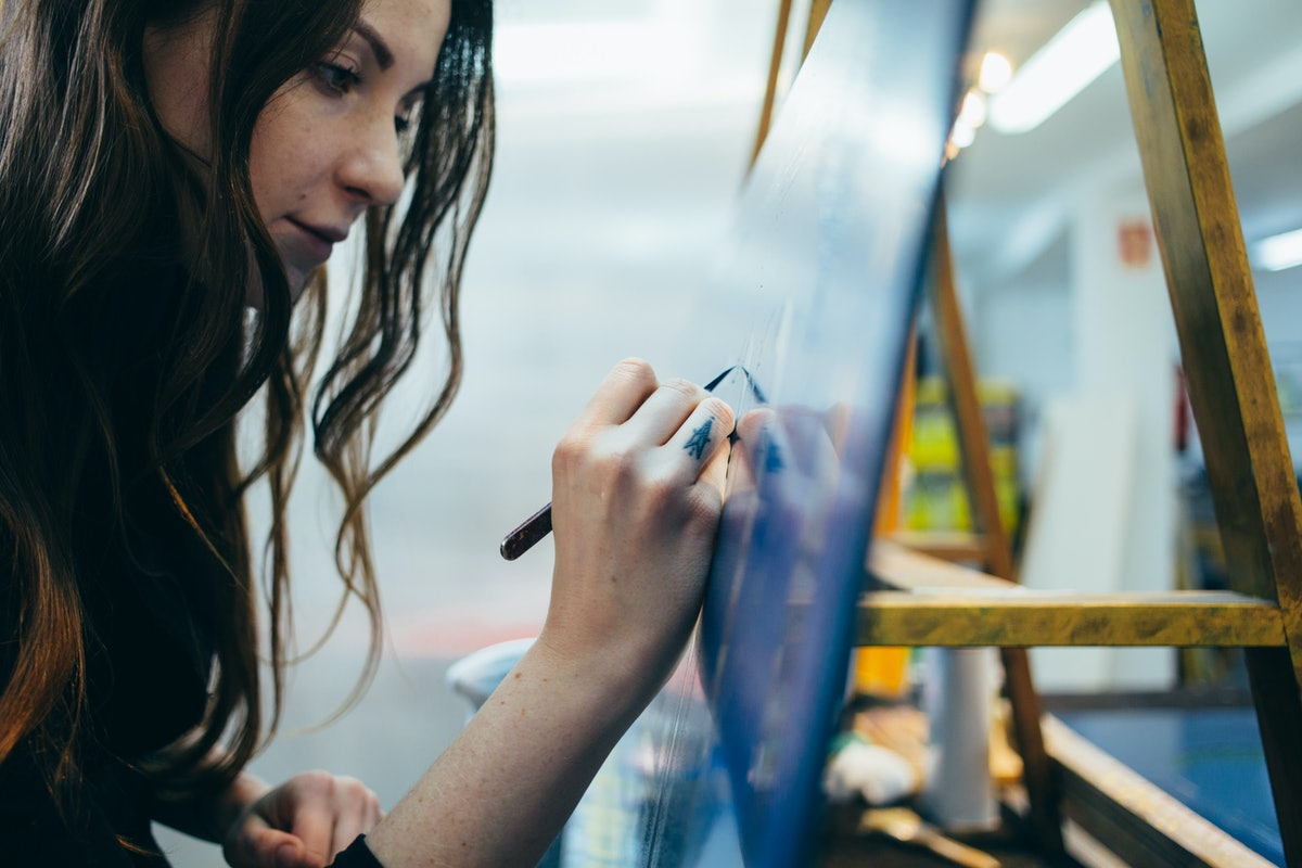 Close up portrait of beautiful and authentic young female artist or painter create art piece. Detail...