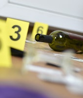Broken glass and bottle of wine marked as evidence during crime scene investigation. Many yellow mar...