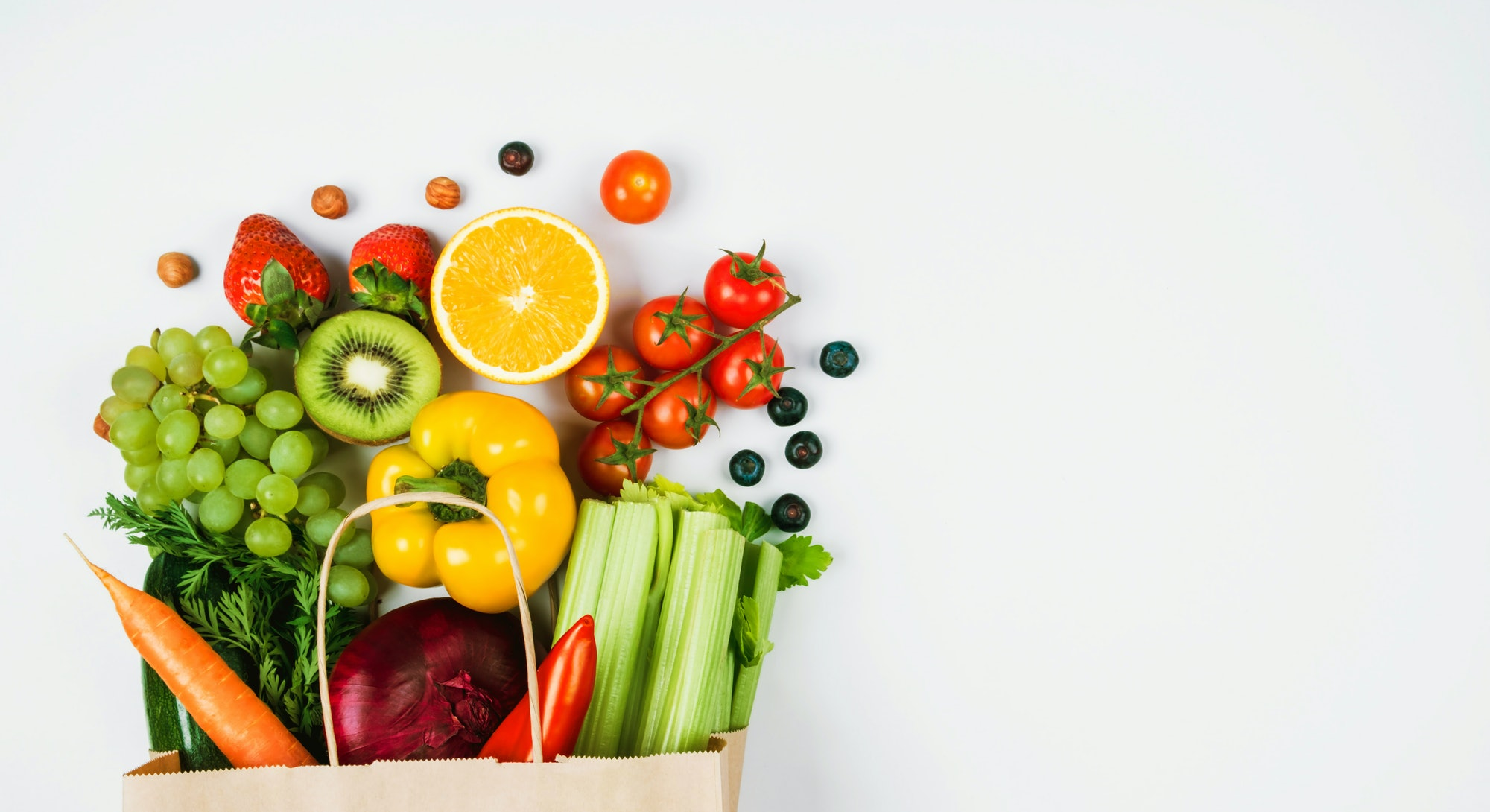 Fruits and vegetables on a light background in a Kraft bag from the store. Healthy and healthy food from the farmers ' market. Space for text