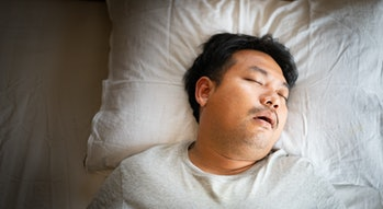 Asian man sleeping on bed with snore face.Concept of snoring.Healthcare medical.Sleep health.Indian ...