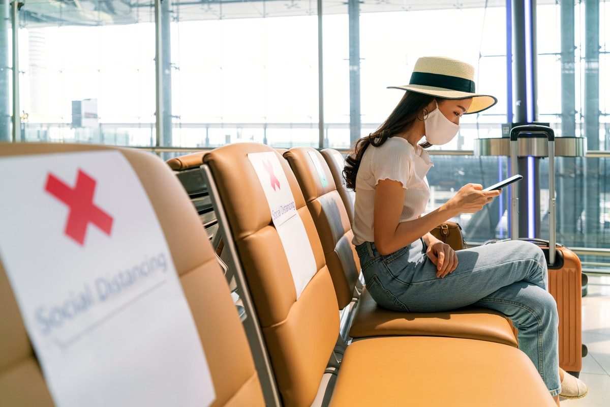 Asian female tourist wearing mask using mobile phone searching airline flight status and sit social distancing chair in airport during coronavirus or covid-19 virus outbreak a new normal concept