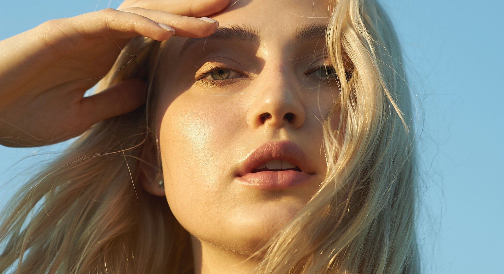 Gorgeous young woman in white romantic clothes on blue sky background. Sunny day. Blonde model with big beautiful eyes and nice lips. Calm and balance. Fashionable look. Beauty portrait. Headshot