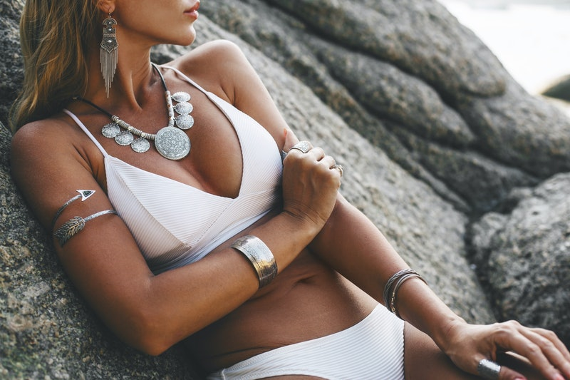 Photo of beautiful boho styled model wearing white swimsuit and silver bohemian jewelery on the beach in sunset
