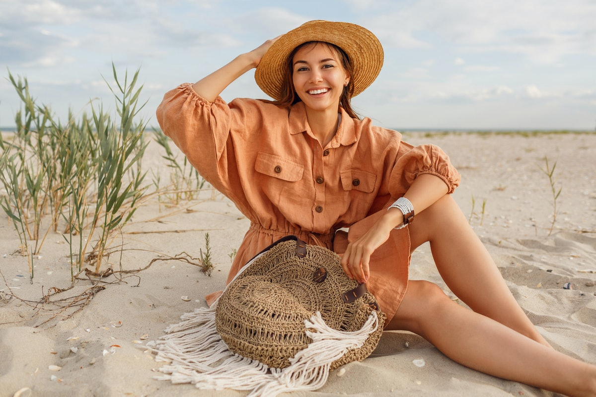 Graceful young  woman in trendy summer linen dress and straw hat posing on the beach near ocean. Bal...