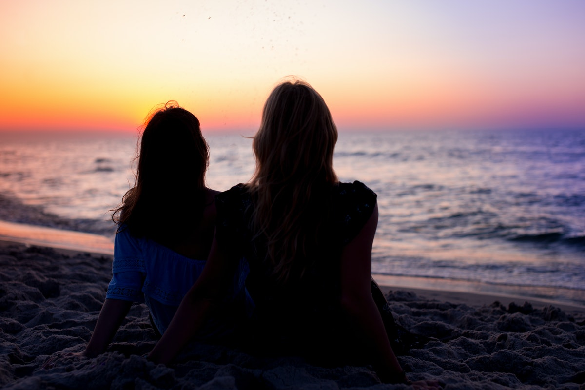 2 friends watching a sunset at the beach before posting a pic on Instagram with a pink sky caption.