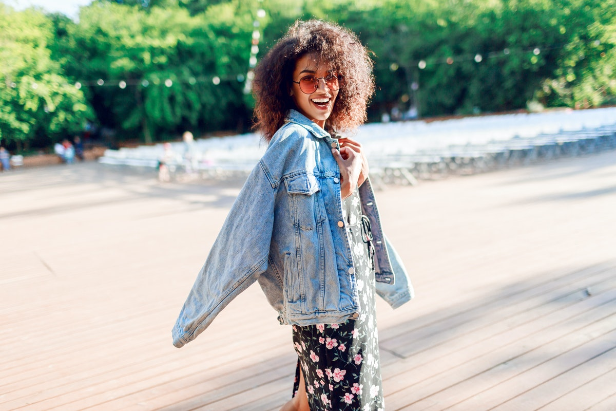 Playful woman wraps herself over her shoulder and looking in camera. Wearing. Stylish hipster outfit. Afro hairstyle . Perfect summer leisure time in the evening park.
