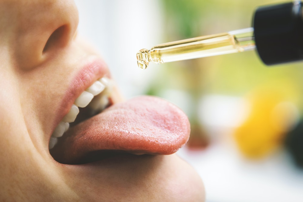 herbal alternative medicine and dietary supplements - woman taking cbd hemp oil drops in mouth from ...