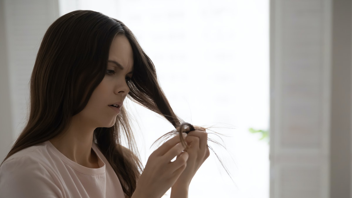 Close up head shot unhappy upset woman checking damaged dry split hair ends, dissatisfied by hairsty...