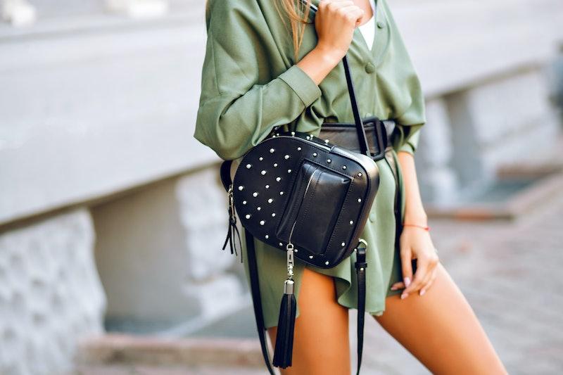 Close up fashion details of woman holding trendy black backpack, wearing mini green dress, minimalis...