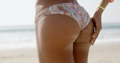 Back view of a sandy woman buttocks on the beach in